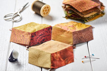 Many diamond pieces of fabric stitched like a cube, developing quilt