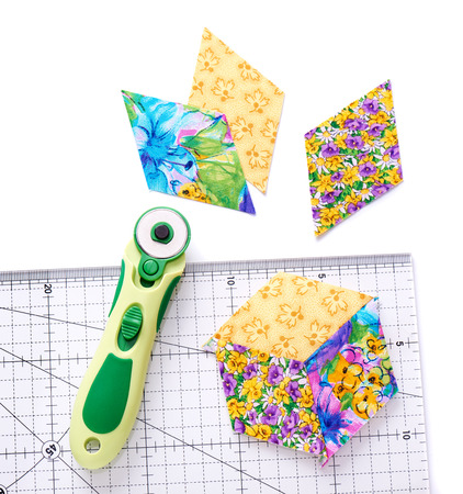 Pieces of quilt with rotary knife and ruler on white surface, top view Stock Photo