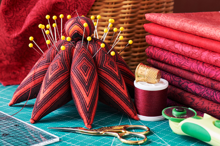 Set of red fabric and sewing tools on craft mat, close-up view Stock Photo