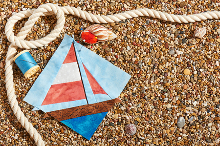Patchwork block, spool of thread, pin cushion and rope lie on sea stones of beach Stock Photo