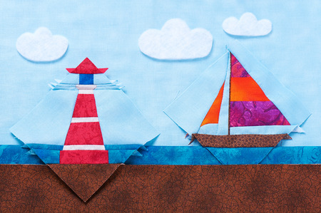Quilting blocks yacht and lighthouse lie on same fabrics like sea landscape