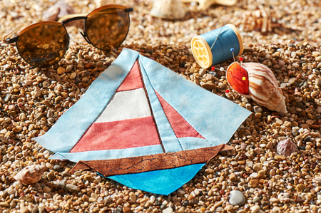 Patchwork block, spool of thread, pin cushion and sunglasses lie on sea stones of beach