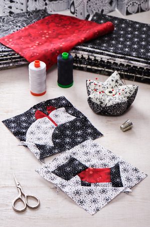 Sewing patchwork of blocks white cat and black dog, sewing accessories Stock Photo