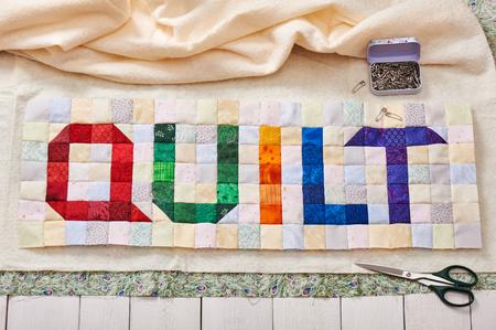 Het woord quilt genaaid van kleurrijke vierkante en driehoekige stoffen