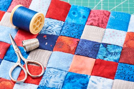 Schaar, draad en vingerhoedje liggend op blauwe en rode vierkante stukjes aan elkaar genaaid