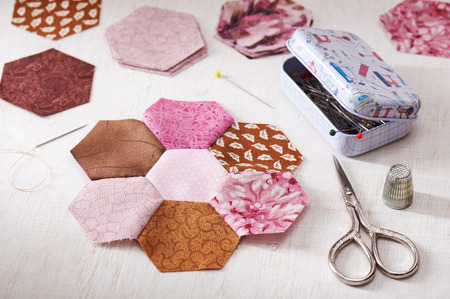 Sewing of hexagon pieces of fabric a quilt Grandmothers Flower Garden Stock Photo