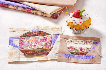 Patchwork blocks of the cup and the teapot with a pattern of flowers and the pin cushion like a cupcake with strawberry Stock Photo
