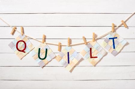 Genaaide letters,? Ombined als het woord quilt, bevestigd met wasknijpers aan een touw op een witte houten achtergrond