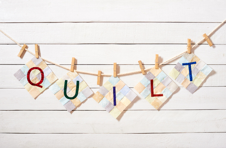 Sewn letters, ?ombined as the word quilt, attached with clothespins on a rope on a white wooden background Stock Photo