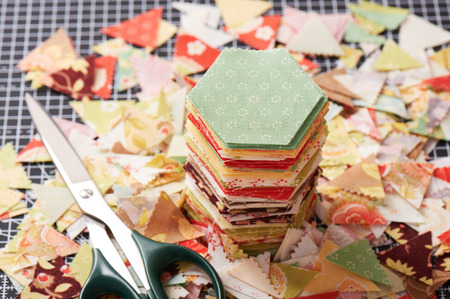 Stack english paper pieced hexagons surrounded by scraps