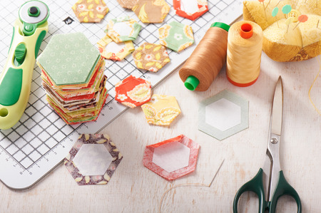 English paper pieced hexagons on white craft mat, sewing equipment