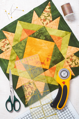 Patchwork orange-green block, quilting fabrics, sewing accessories Imagens