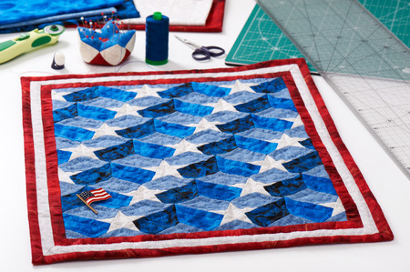 Completed quilt with stylized elements of American flag, patchwork tools