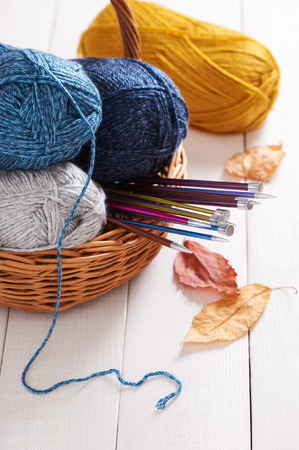 Skeins of yarn and knitting needles in basket