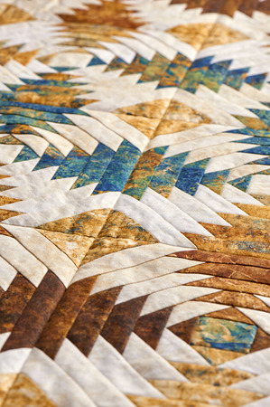 Fragment of quilt stitched from pineapple pattern blocks, traditional patchwork Фото со стока