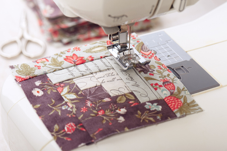 Patchwork log cabin blocks on electric sewing machine, stack of blocks, sewing accessories Imagens