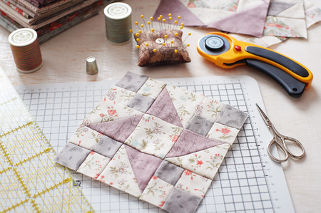 Patchwork block on craft mat, stack of fabric, sewing accessories on white wooden surface Banque d'images