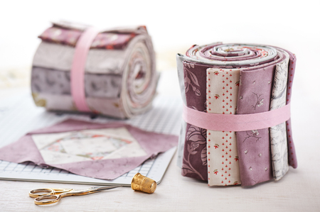 Patchwork block on craft mat, rolls of fabric, sewing accessories on white wooden surface 스톡 콘텐츠