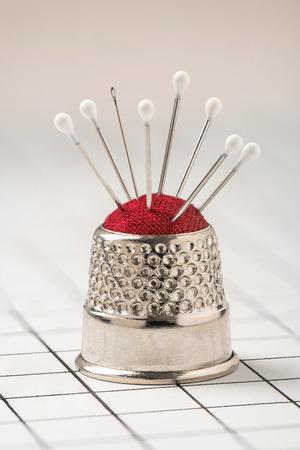 Pin cushion stylized like thimble with pins and needle, macro Imagens