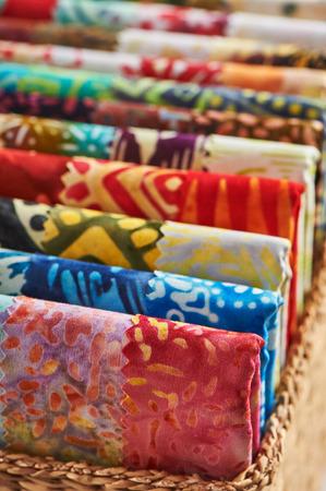 Folded bright pieces of quilting batik fabrics in a basket, macro Stok Fotoğraf
