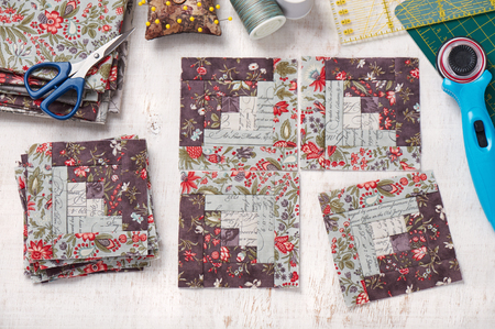 Patchwork log cabin blocks, stack of blocks, sewing accessories on white wooden surface Imagens