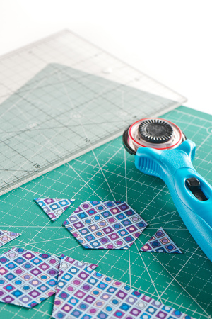 The process of cutting pieces of fabric in the shape of hexagons to create a quilt