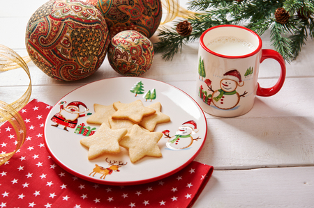 Cookies in the shape of a star on a Christmas plate and milk in a Christmas cup Standard-Bild