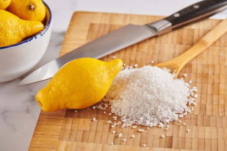 Lemon and pile of coarse sea salt on cutting board