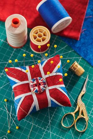 Pincushion like Union Jack on green craft mat, sewing accessories