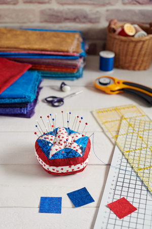 Pin cushion stylized elements of American flag, stacks of fabrics, quilting accessories Stock Photo