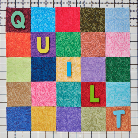The word quilt composed of colored wooden letters laid out on colorful pieces of fabrics arranged in shape of square