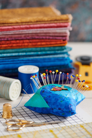 Quilting accessories on the background of a stack of bright quilting fabrics Stock Photo