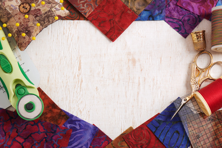 Quilting accessories forming a heart shape on a white wooden surface