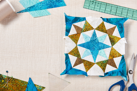 Patchwork block and sewing accessories on white wooden surface Imagens