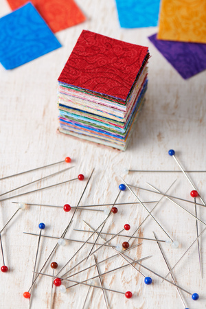 Stack of square pieces of colorful fabrics and heap of multicolor ball head sewing pins