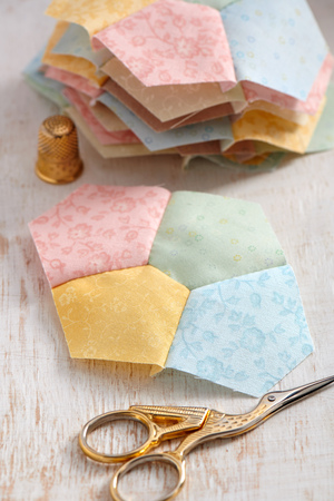 Stitched quilting block from four pentagons, scissors, thimble, pile of blocks
