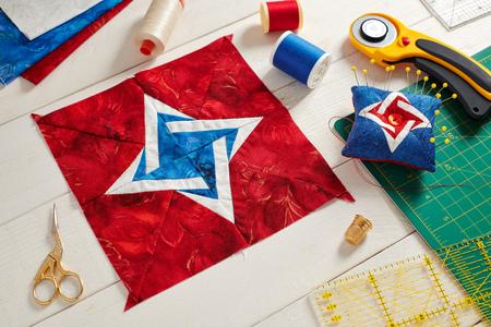 Bloque de patchwork, cojín de alfiler y accesorios de acolchado sobre superficie de madera blanca Foto de archivo