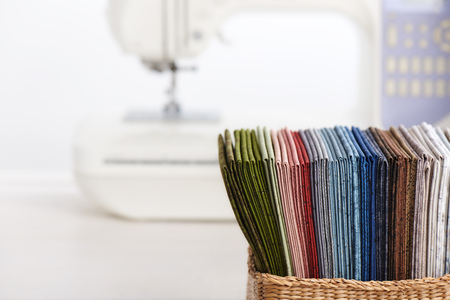 Stack of colorful quilting fabrics in basket on the background of sewing machine Imagens - 122927390