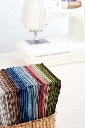 Stack of colorful quilting fabrics in basket on the background of sewing machine Imagens - 126858822