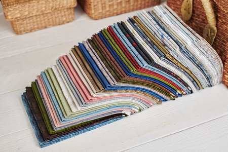 Stack of fat quarters of colorful quilting fabrics on the background of baskets