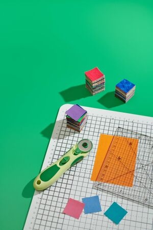 Rotary cutter, ruler, bright square pieces of fabric, stack of bright square fabric pieces on craft mat, green background Banque d'images