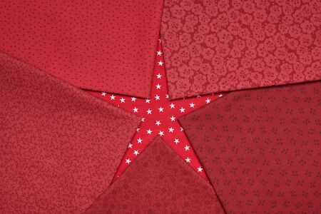 Fat quarters of fabrics red colors lying in the shape like a star on red fabric with white stars pattern