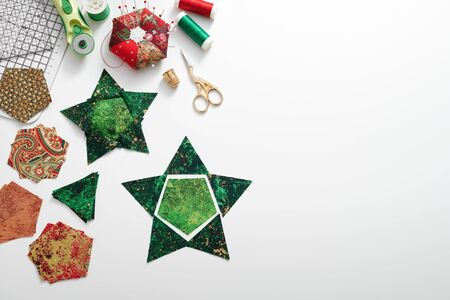 Preparation of pentagon and triangular pieces of fabric for sewing patchwork star, quilting accessories. Space for text