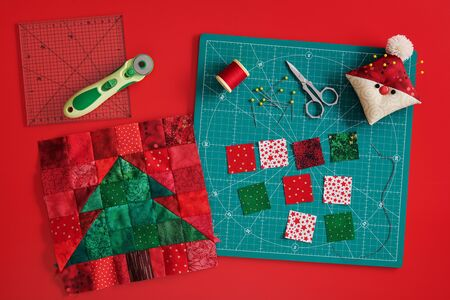 Christmas tree patchwork block, craft mat, bright square pieces of fabric, pincushion like Santa and quilting accessories on red background Stock Photo