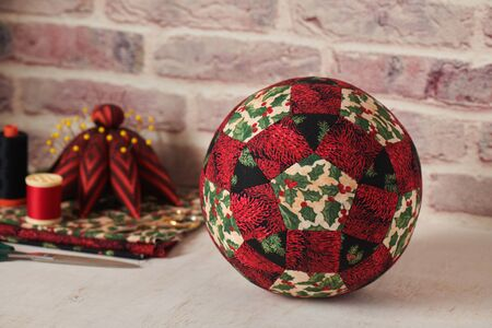 Christmas decoration ball sewn from pieces of fabrics, sewing accessories, traditional patchwork