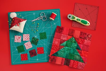 Christmas tree patchwork block, craft mat, bright square pieces of fabric, pincushion like Santa and quilting accessories on red background 写真素材