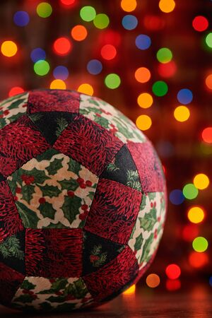 Christmas decoration ball sewn from pieces of fabrics on dark colorful bokeh background Imagens