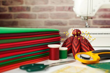Stack of red and green fabrics, sewing and quilting accessories and sewing machine on brick wall background Imagens