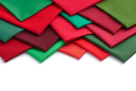 Heap of red and green fabrics on white background, space for text