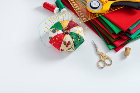 Pile of red and green fabrics, pincushion, sewing and quilting accessories on white background, space for text 免版税图像